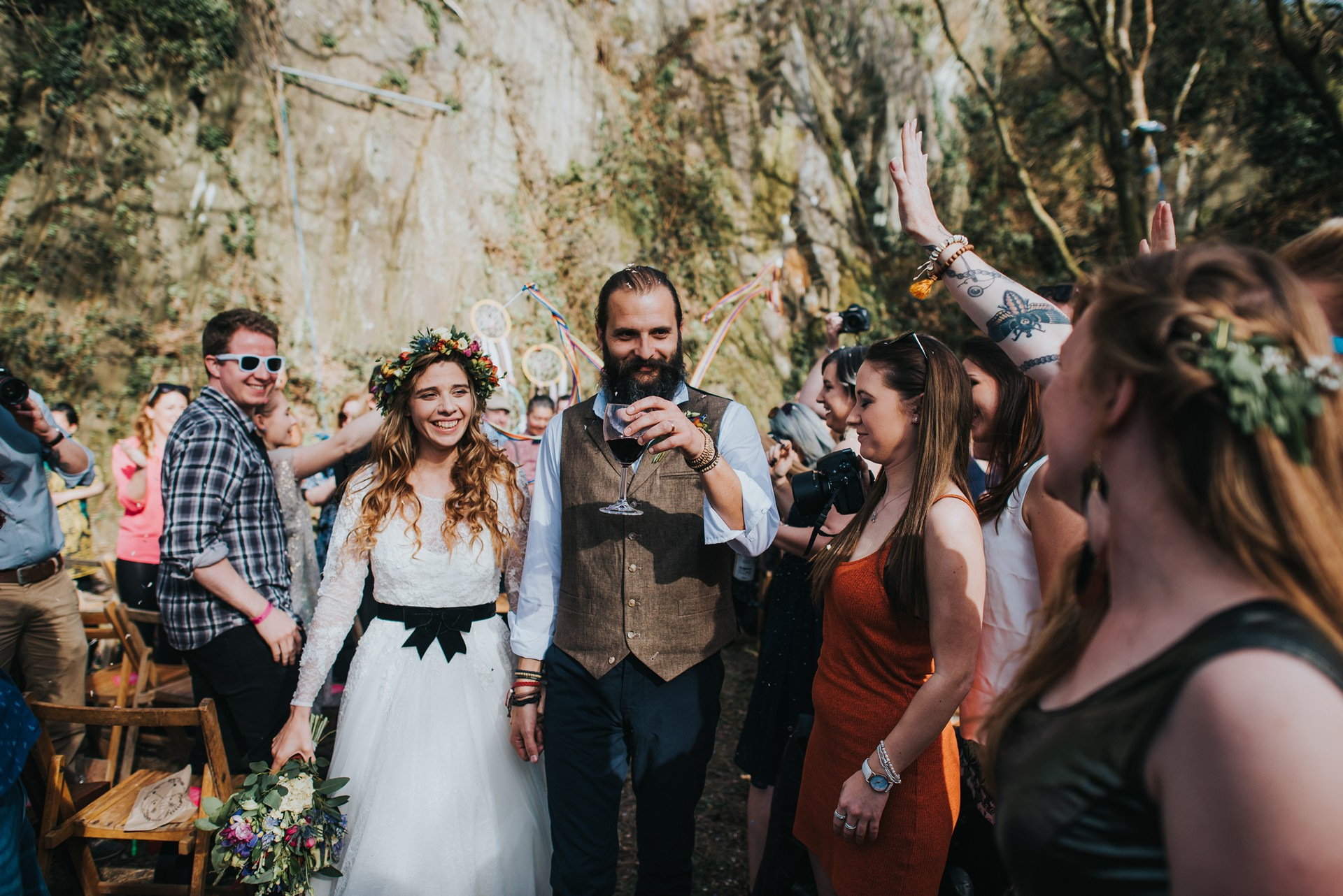 Boho flower crown bride walking down the isle with groom holding a glass of red wine