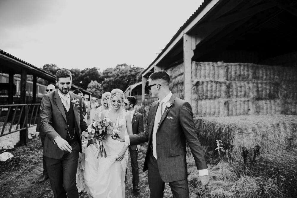 bride enjoying a beer on wedding day