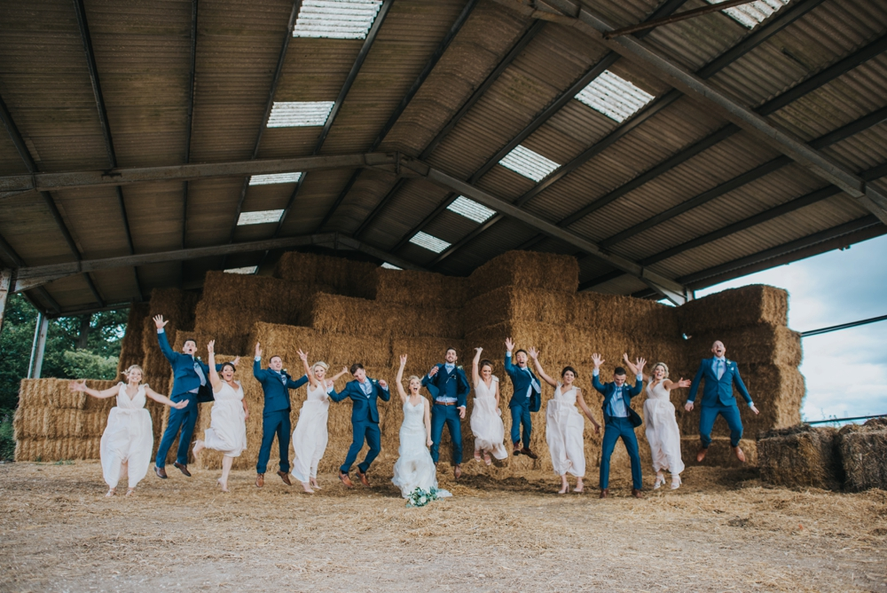 wedding party and friends jumping in hay barn