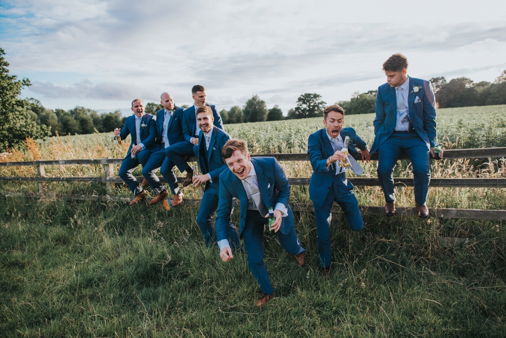 guys falling off fence at wedding