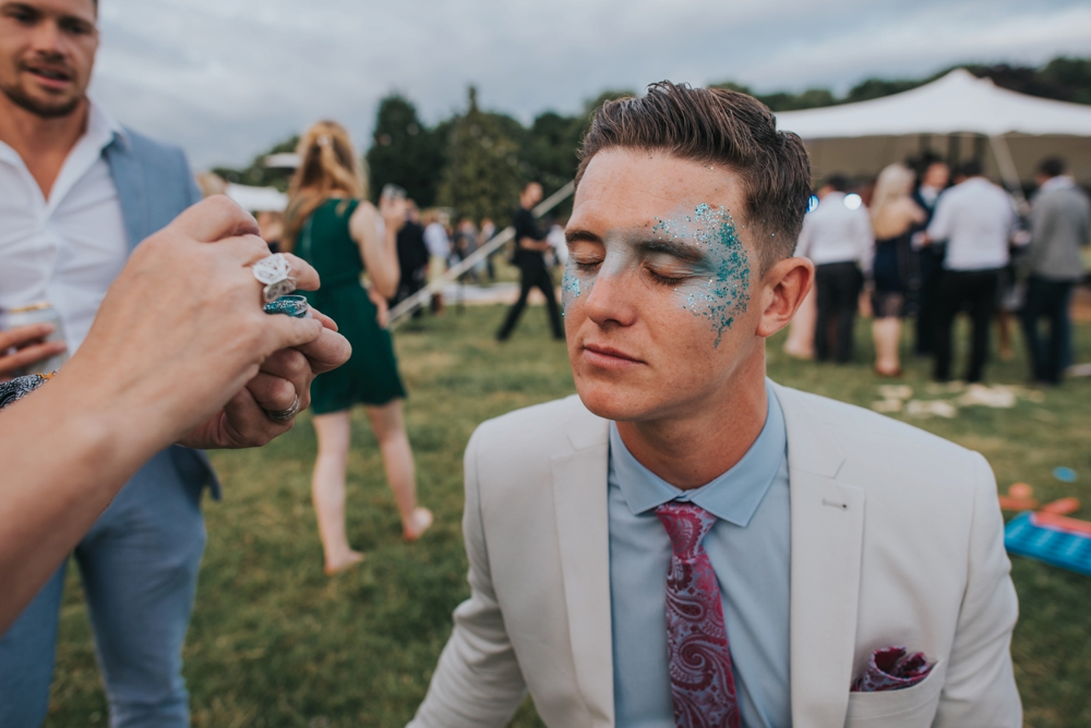 man getting face painted at festival wedding