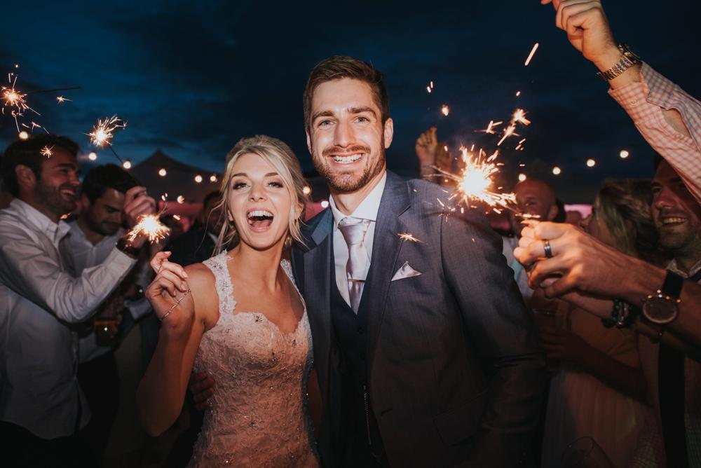 bride groom holding sparklers at festival wedding