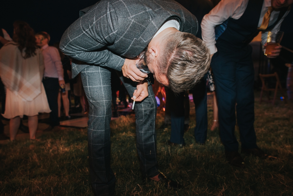 boy throwing up in cup at festival wedding