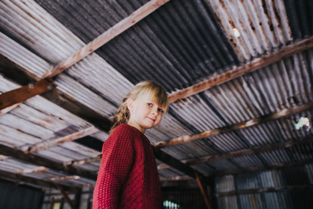 girl in red jumper in shed