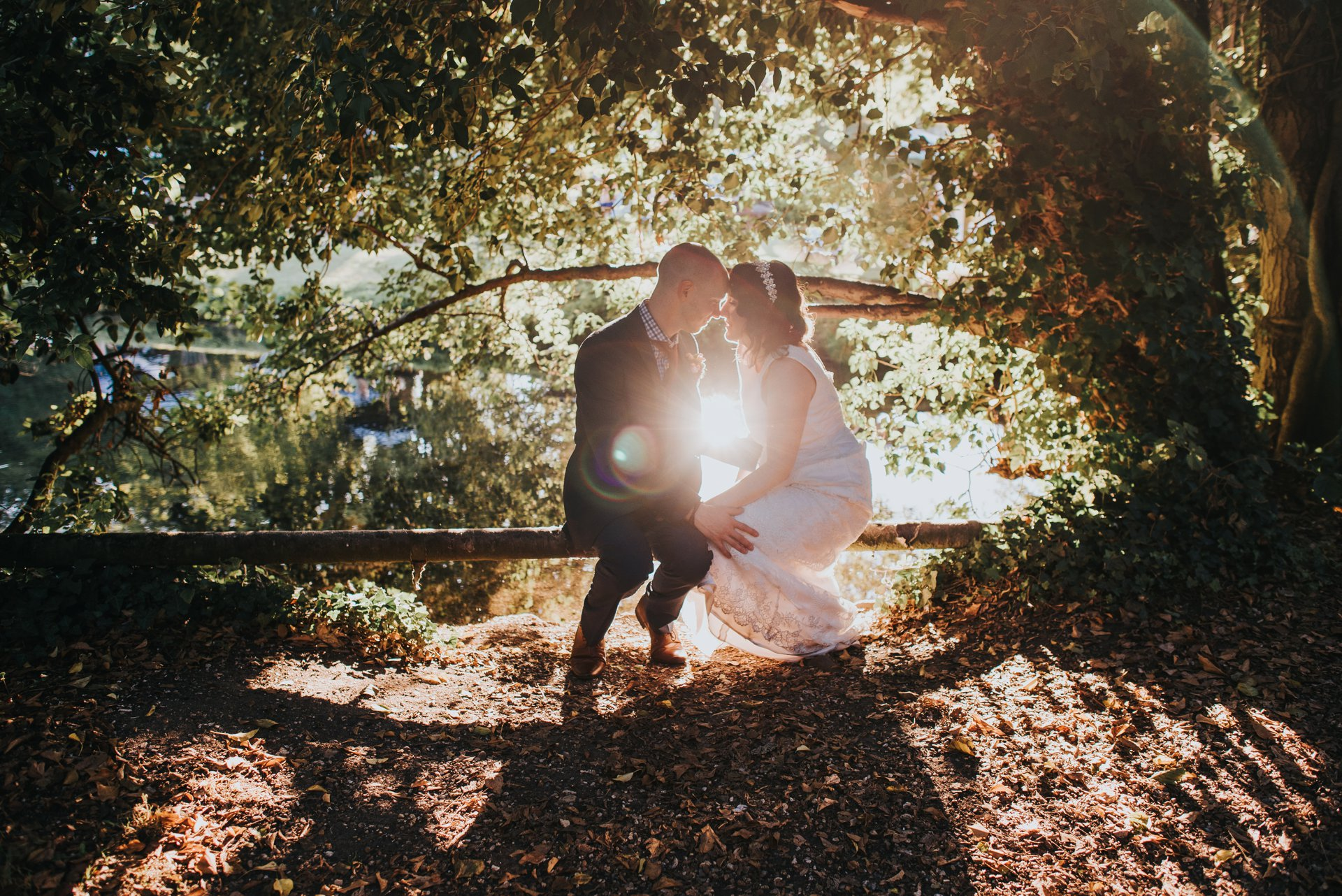 bride and groom sitting by river in golden hour
