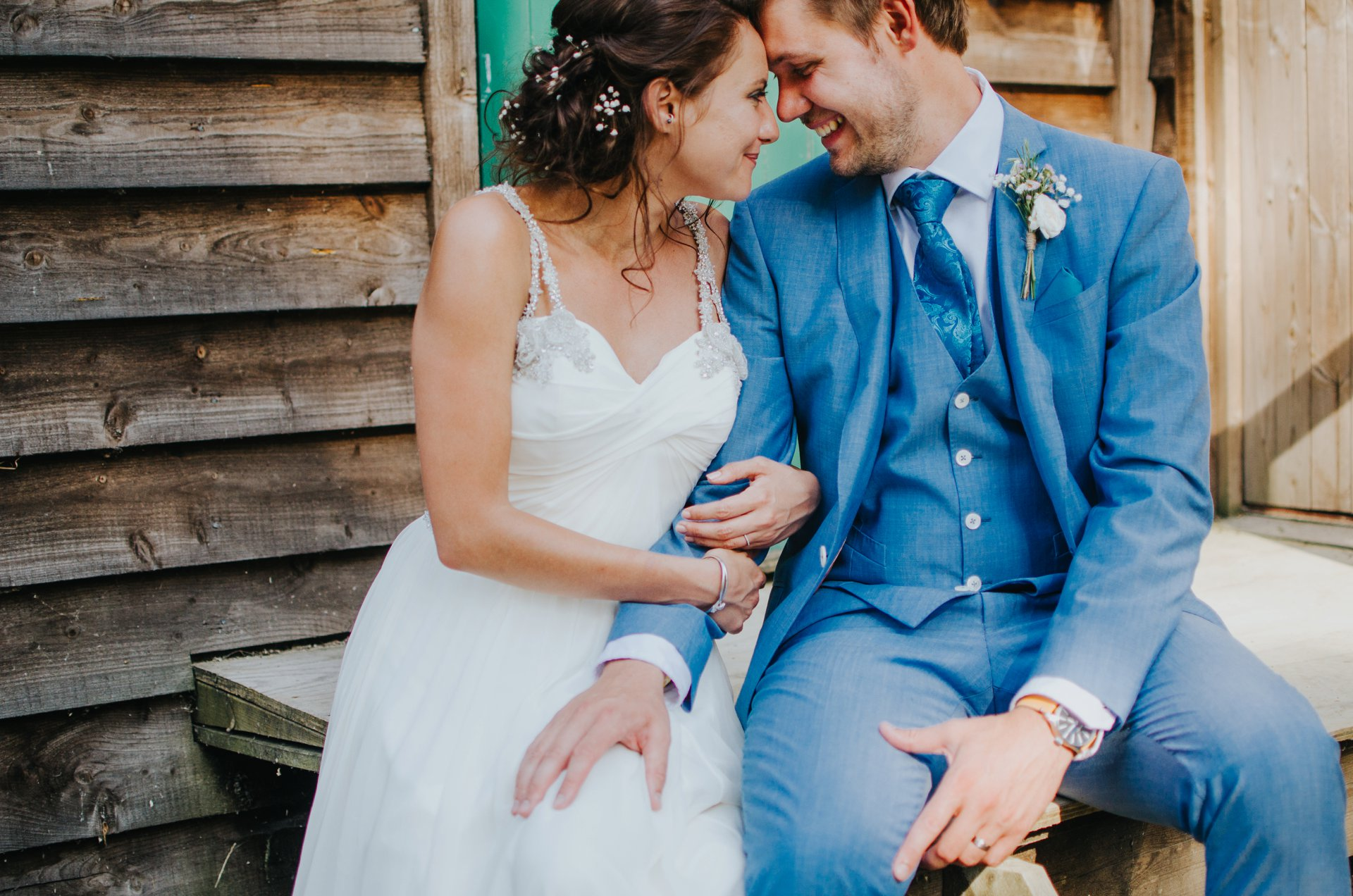 stylish bride and groom in blue suit sitting holding hands on wedding day