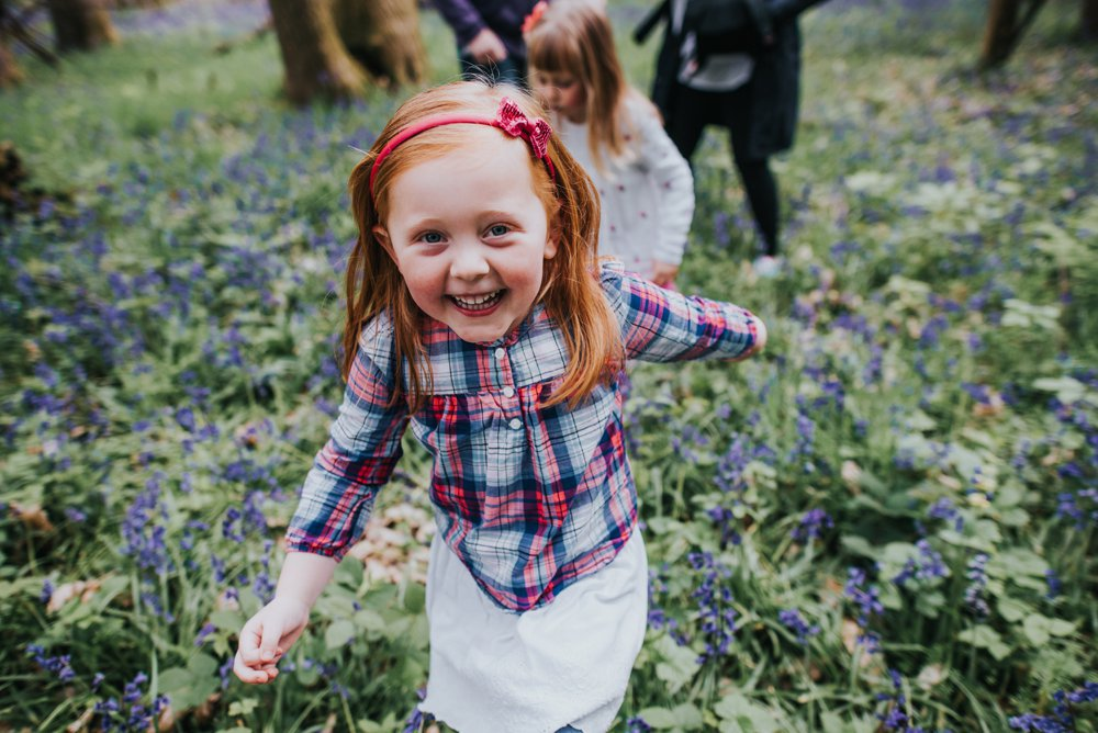 red head girl walking though bluebells
