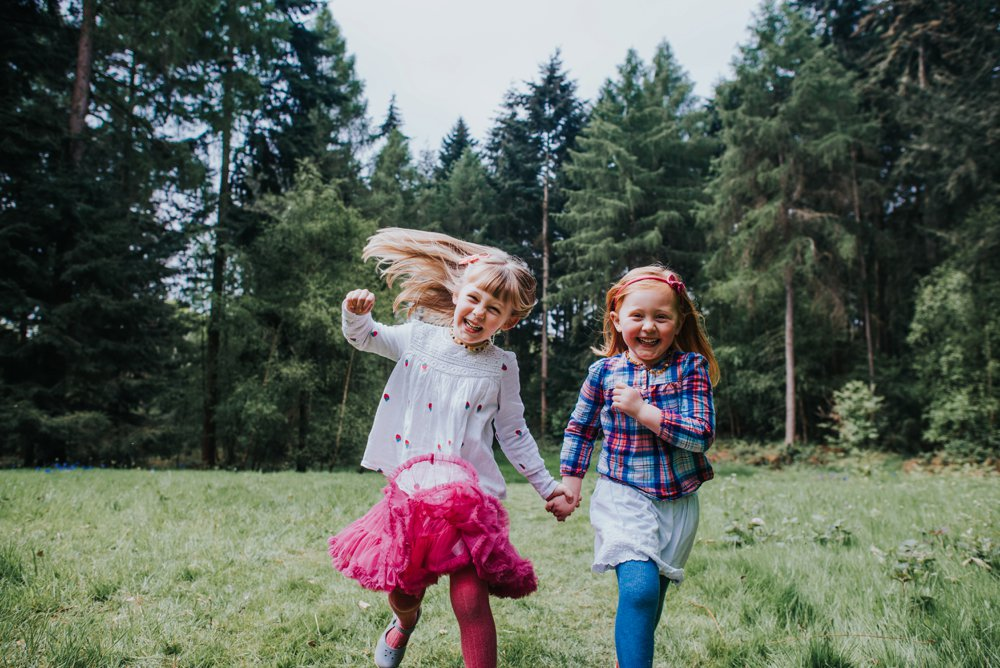 sisters running through woods holding hands