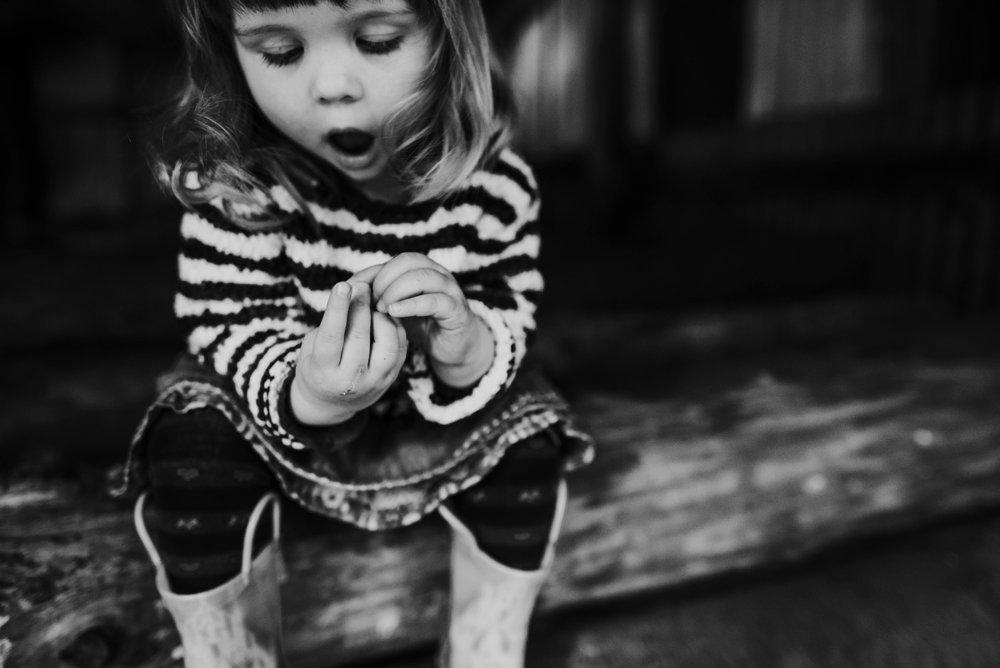 toddler girl sat on a log wearing wellies