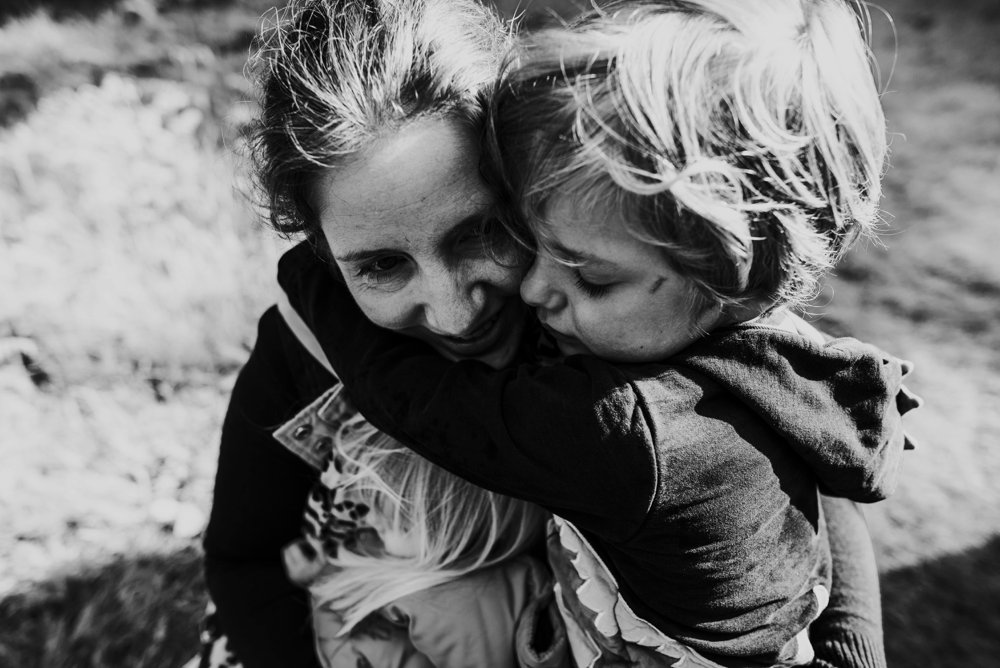 mum hugginer her two children in a field