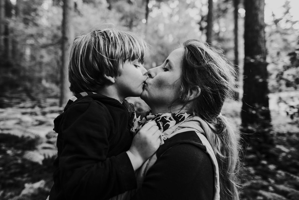 caring moment mother and son sharing a kiss
