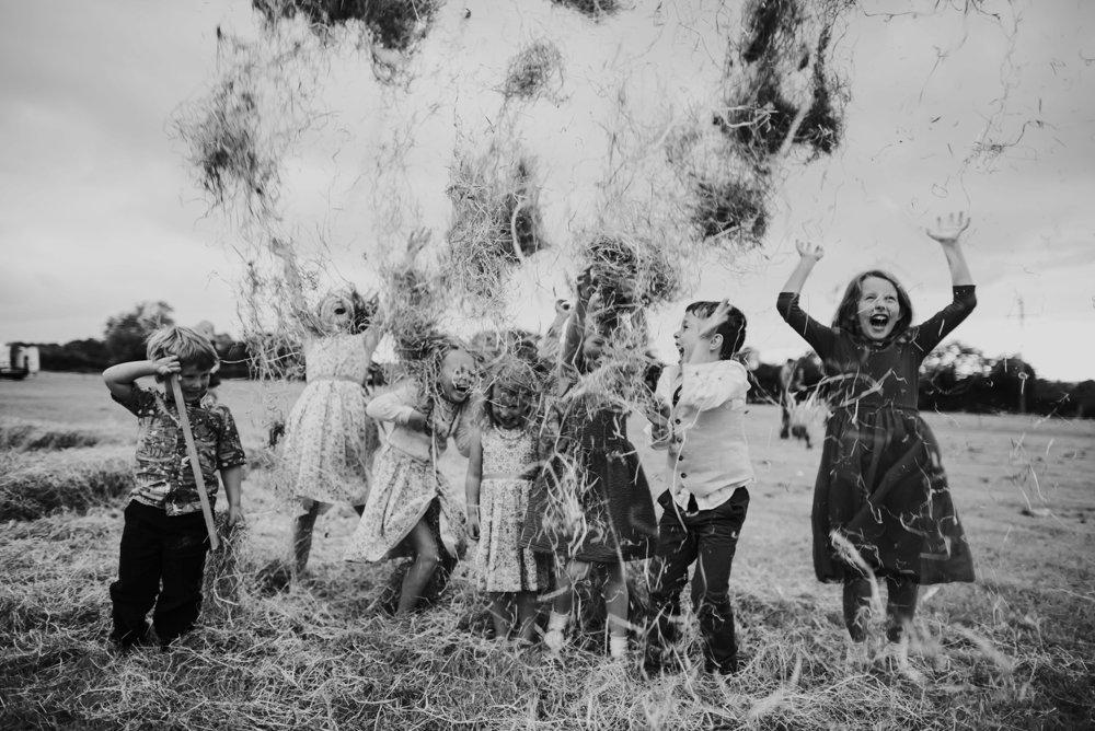 group of kids throwing hay