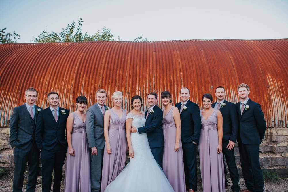 bridal party standing infront of organge shelter