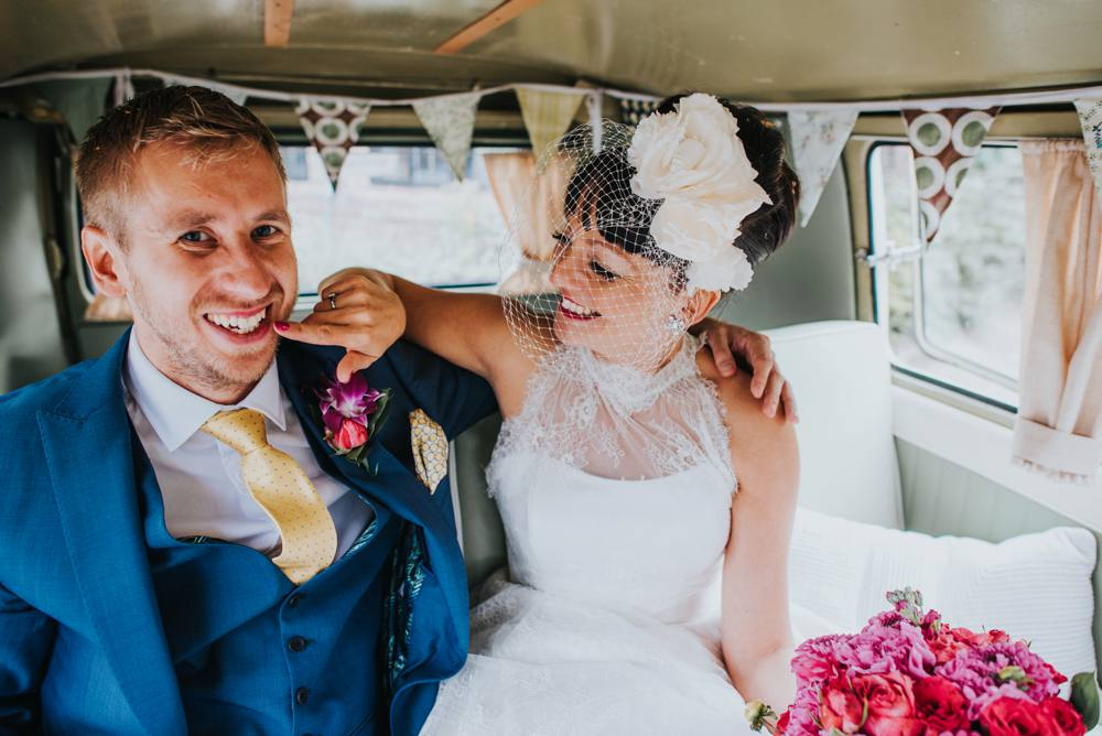 bride and groom sitting inside a VW camper