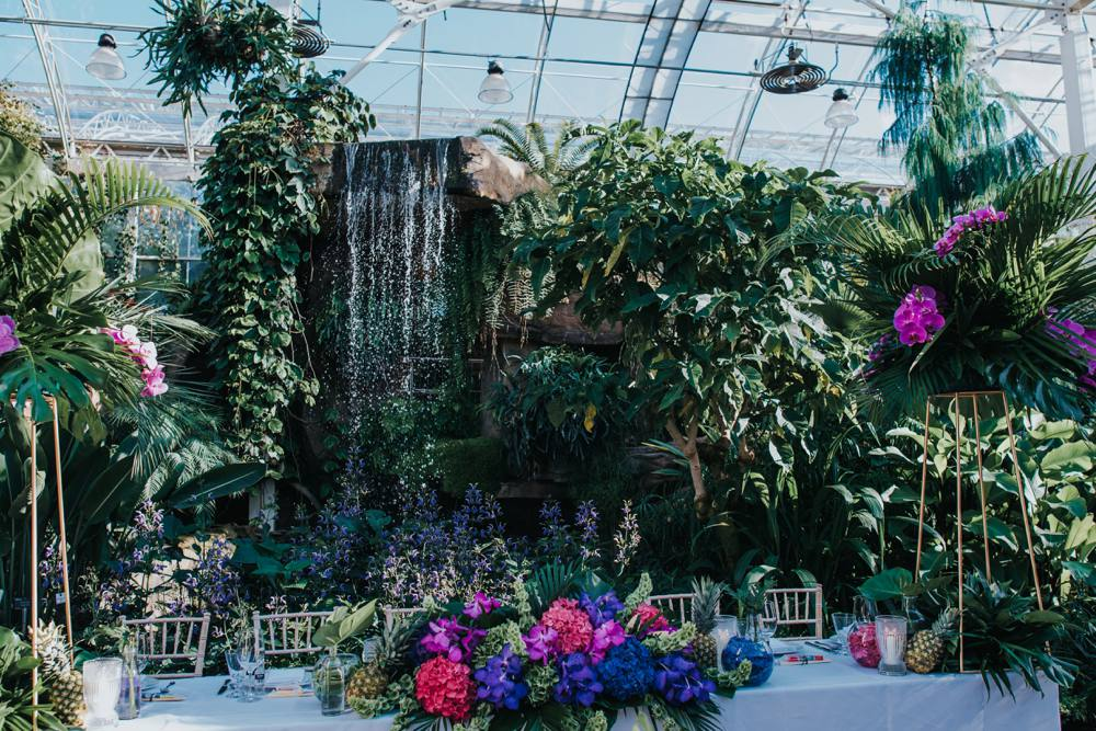tropical themed glasshouse wedding with waterfall