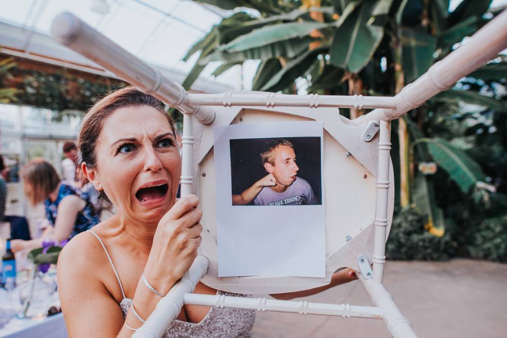 Bridesmaid holding up chair with embarassing photo hidden