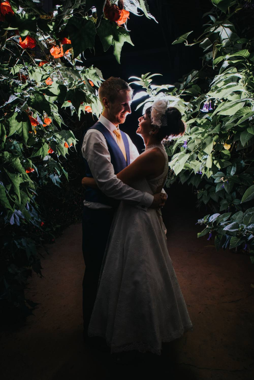 bride and grrom hugging at night in glass house
