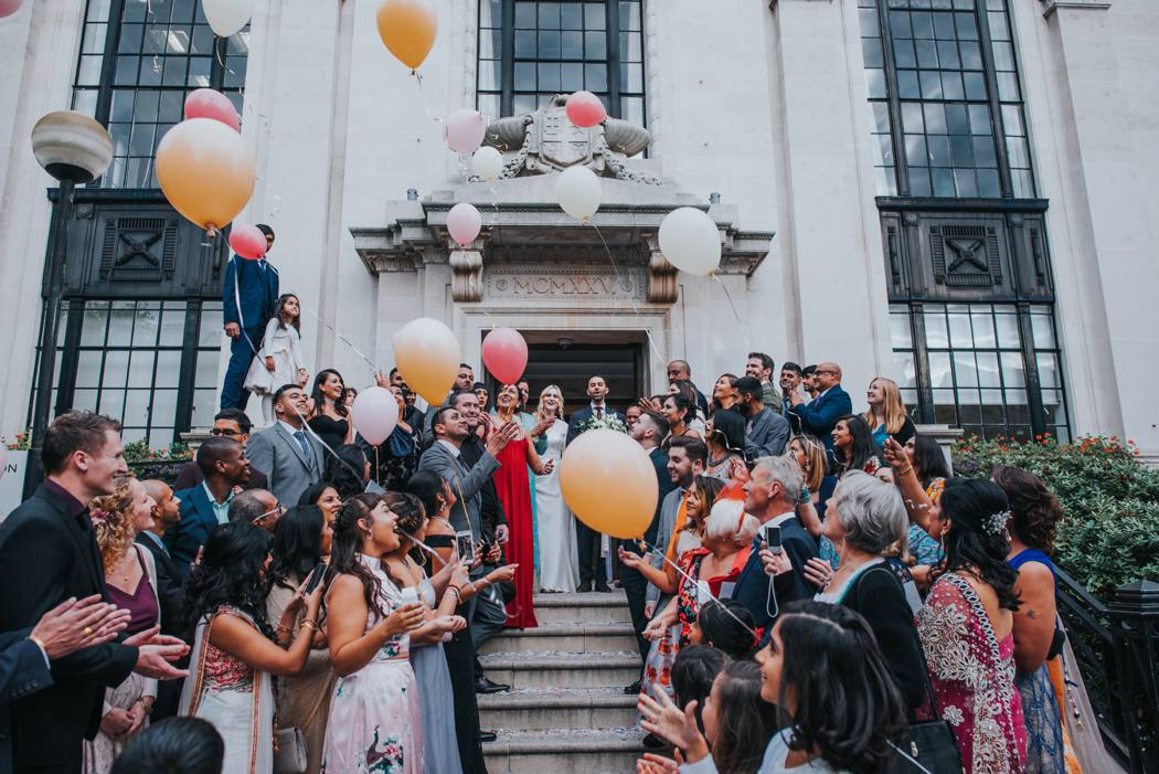 wedding guests on islington town hall steps with balloons