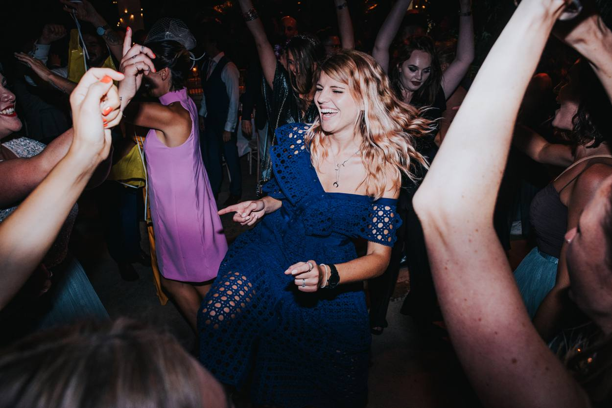 girl in blue dress dancing at wedding