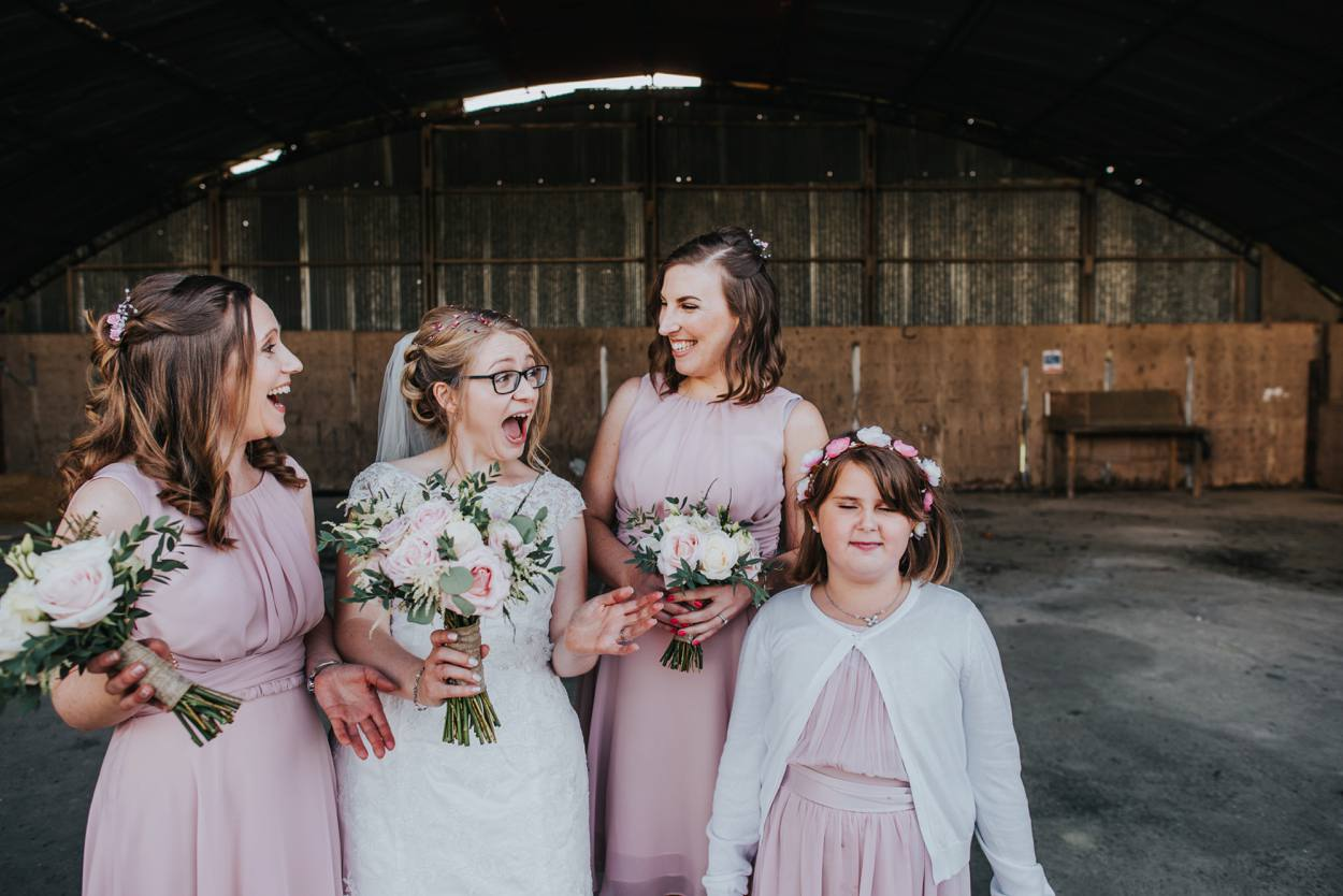 bride and bridesmaids standing in barn