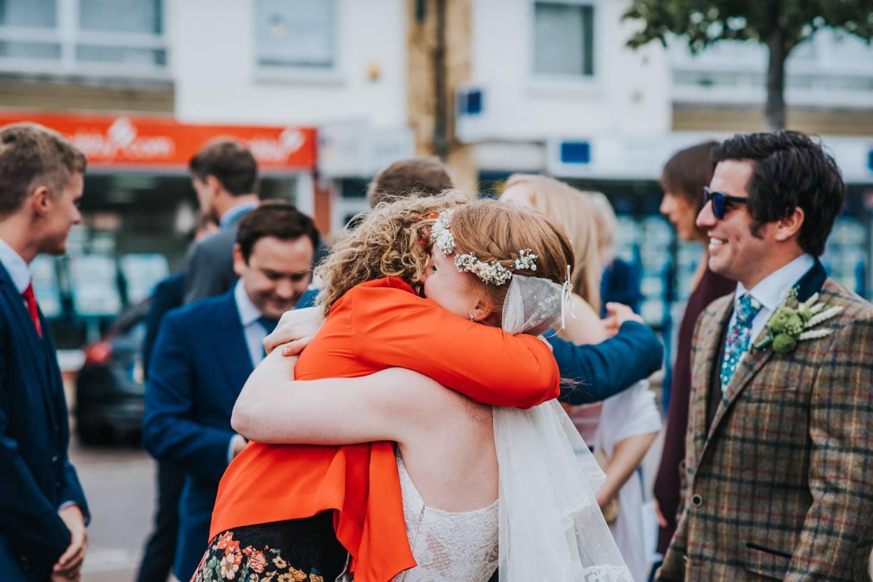 bride hugging her best friend after ceremony