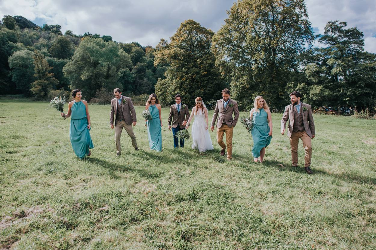 boho bridal party walking through field