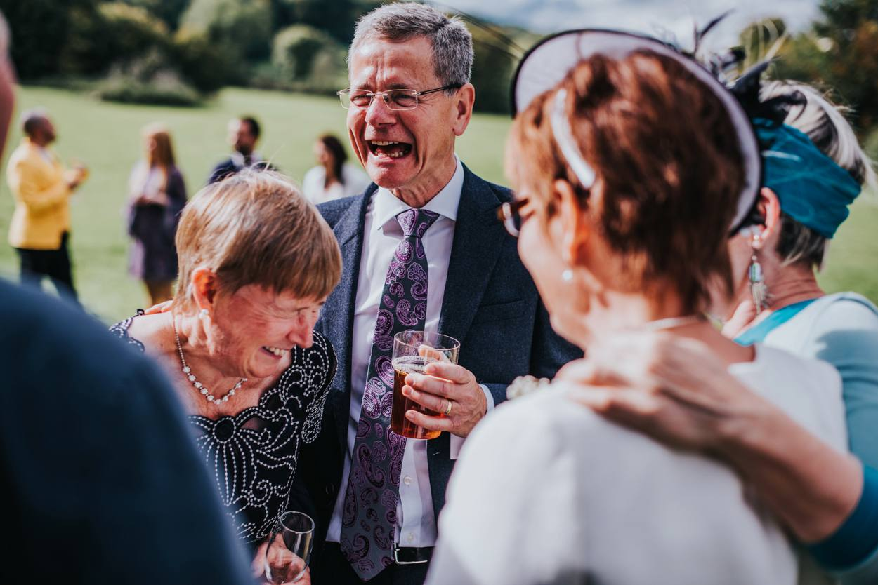 man telling wedding guests joke