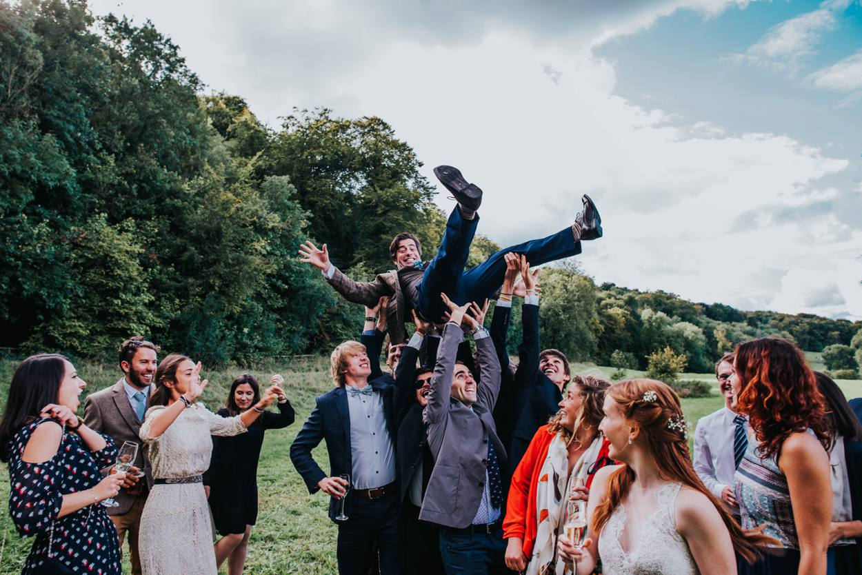 groom being liefted in the air by wedding guests