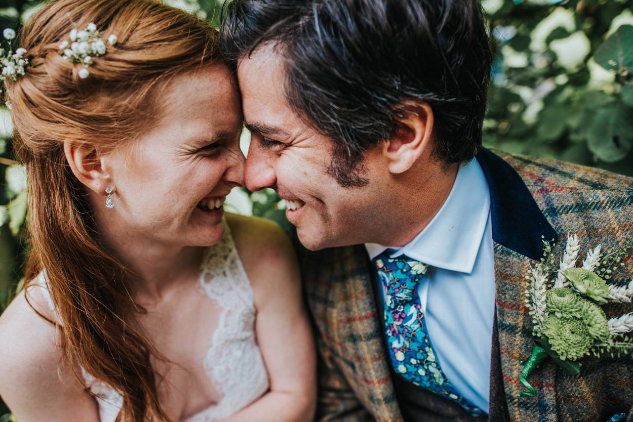 boho bride and groom in tweed suit cuddling on wedding day