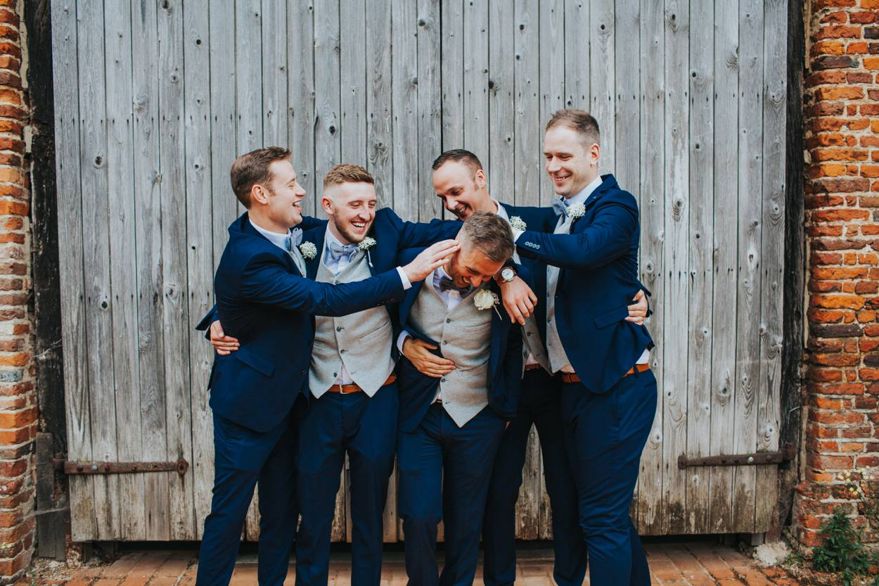 groom in blue suit and tweed waistcoat with friends