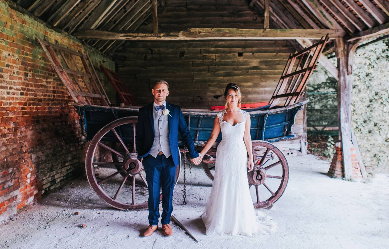 bride and groom holding hands in front of horse cart