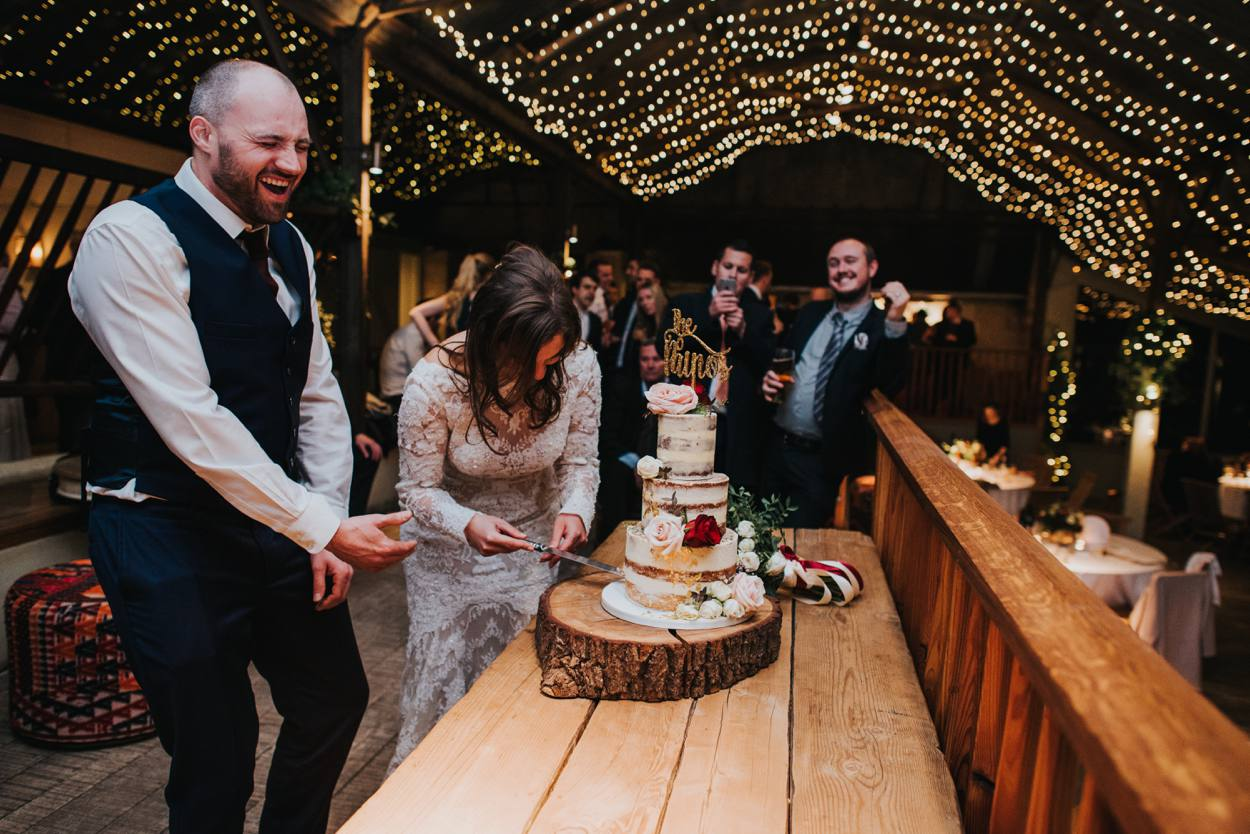 bride and groom laughing cutting cake