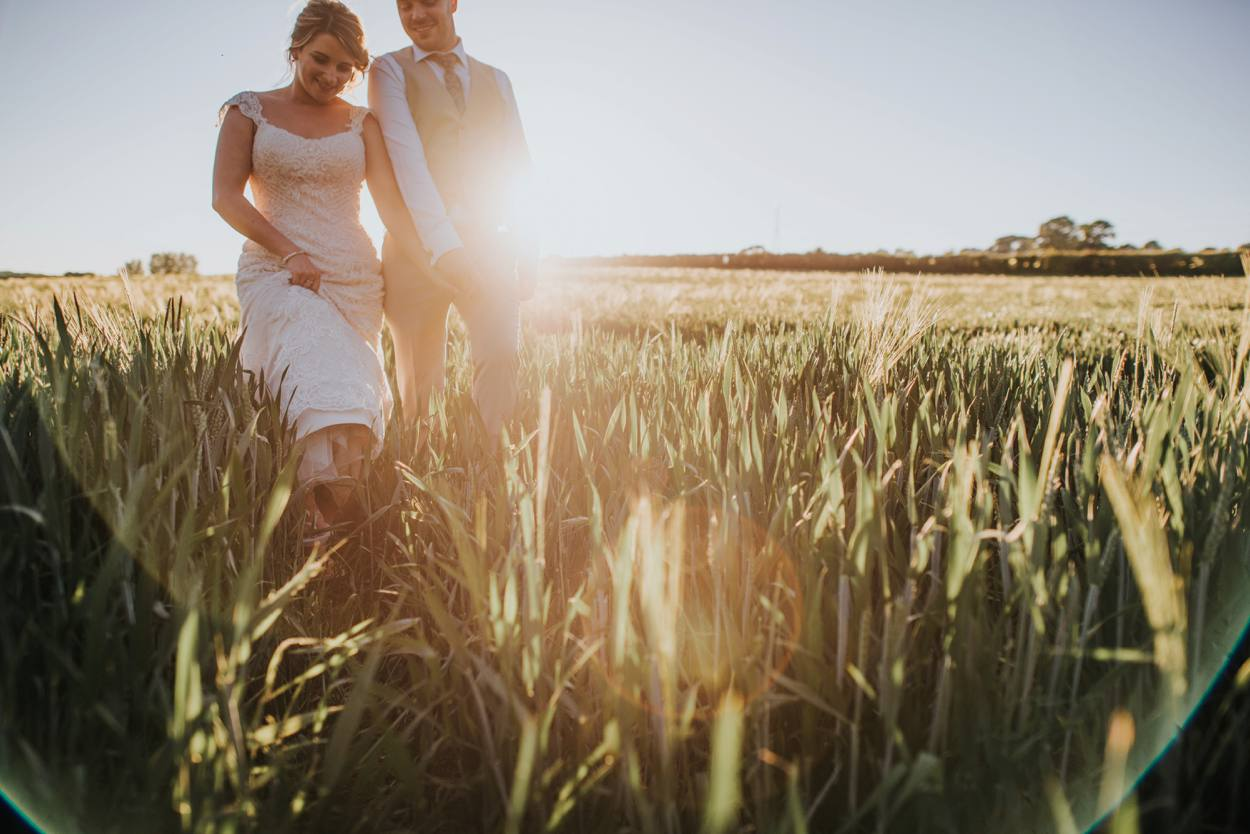 bride and groom walking through corn field in summer light