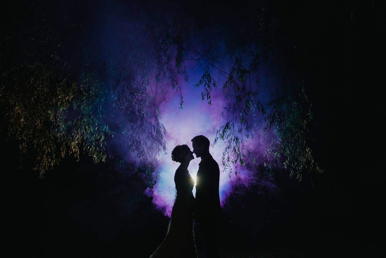 bride and groom in front of smoke bomb, watermill theater