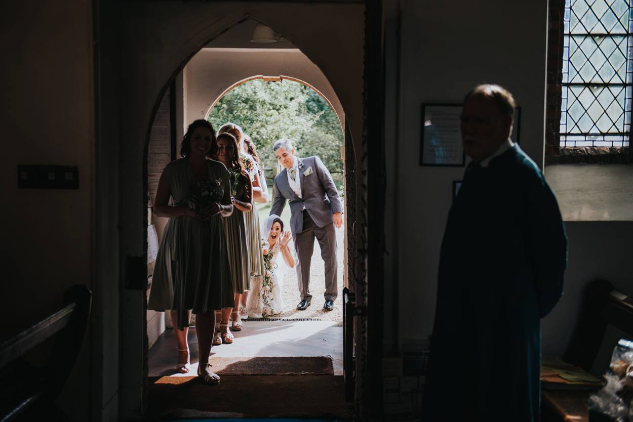 bride waving to guests inside church