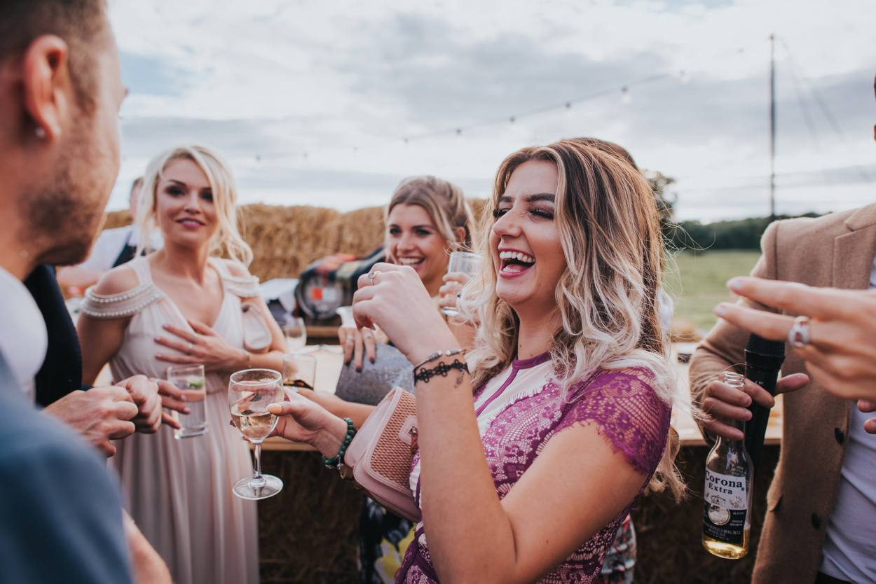 girl drinking shots with friends at wedding