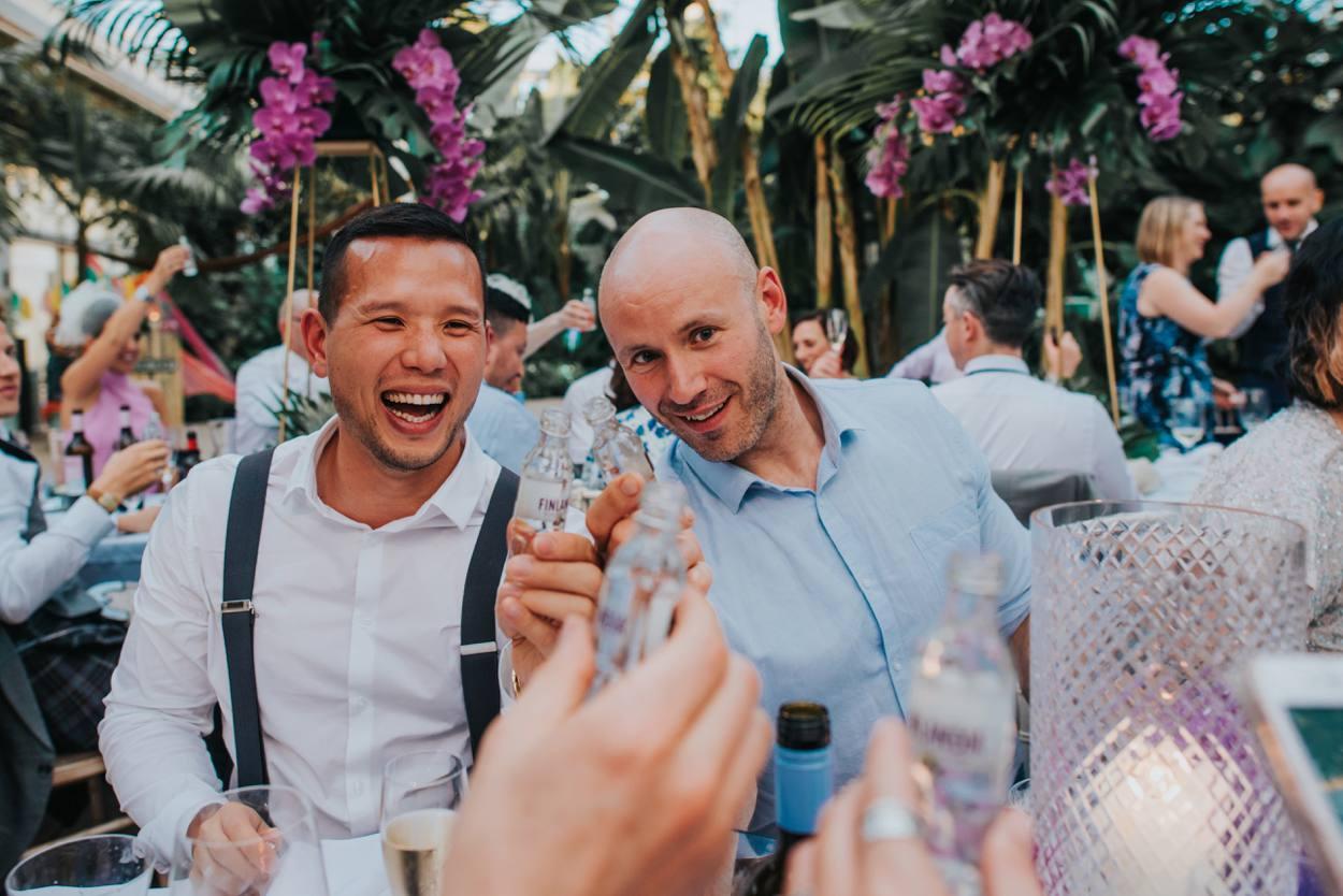 2 men doing vodka shots at wedding RHS Wisley