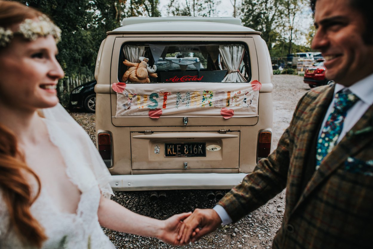 boho bride holding hands with groom by VW camper