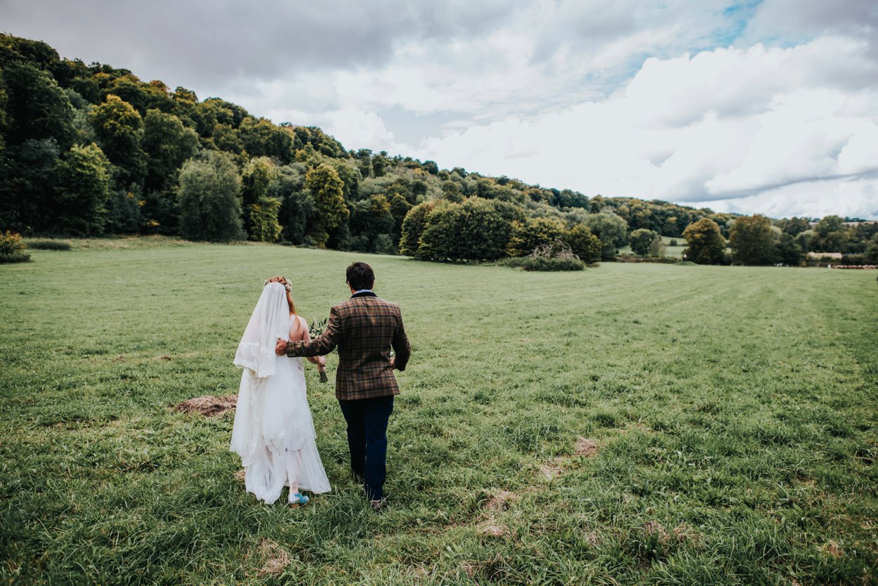 boho bride and groom by walking in field