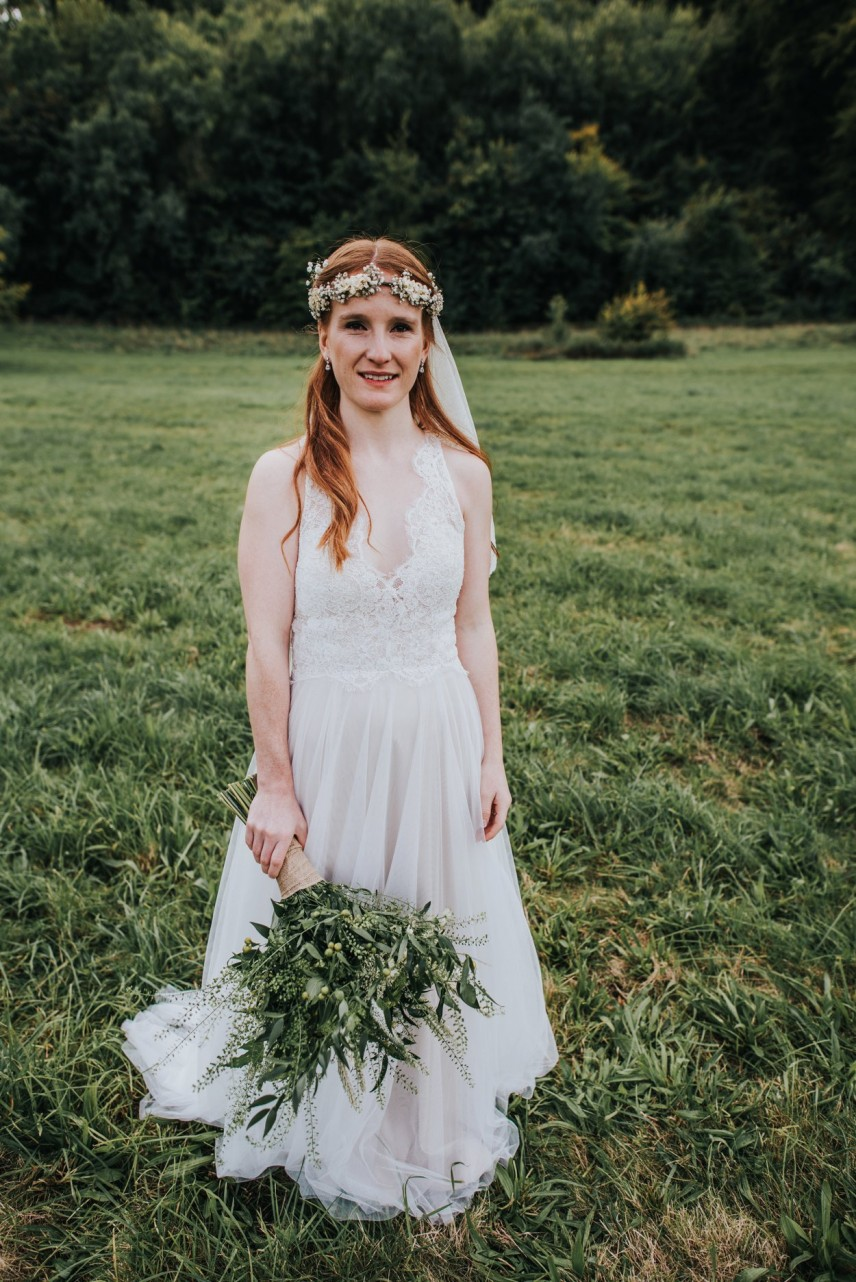 boho red-headed bride standing in field with oversized bouquet