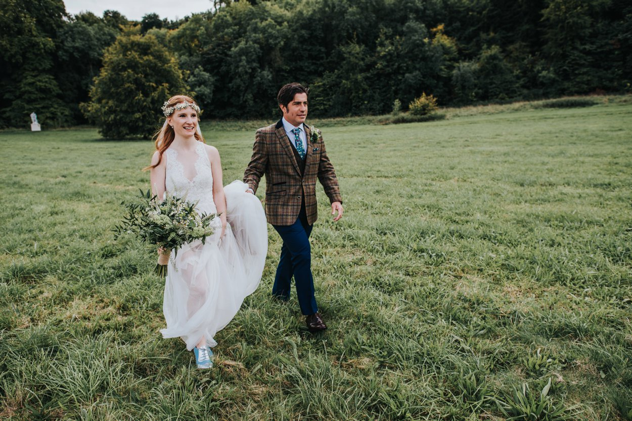 boho red-headed bride and groom walking in field with oversized bouquet
