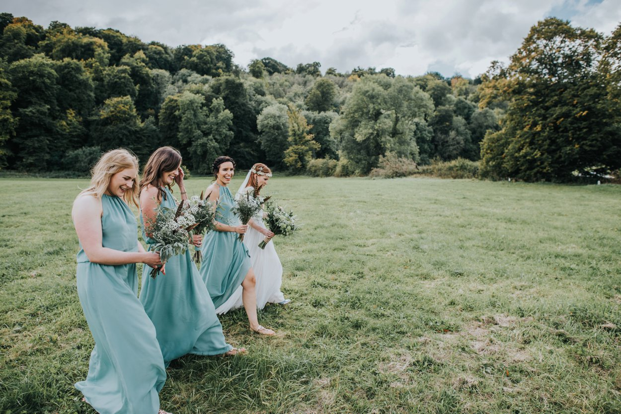 Bogo Bride and bridesmaids walking in field