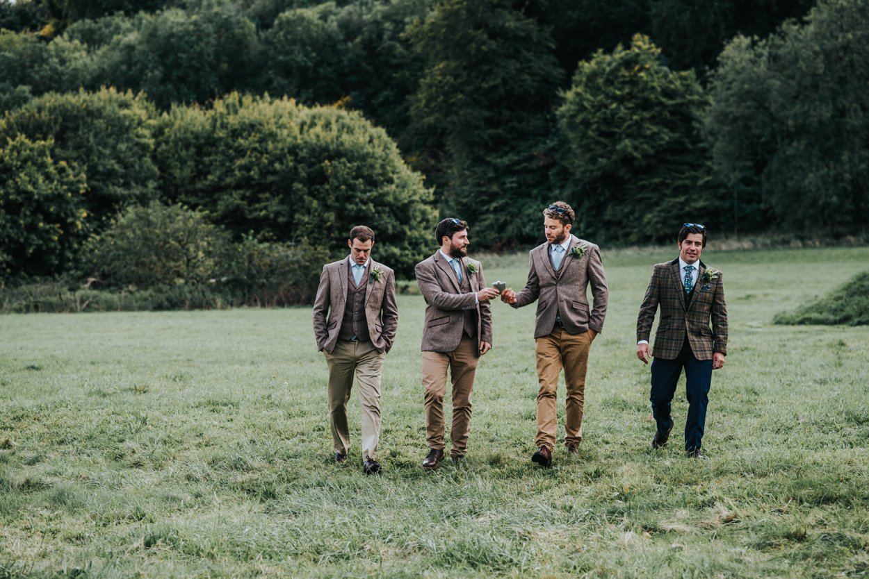 Groom and ushers in tweed suits walking in field drinking
