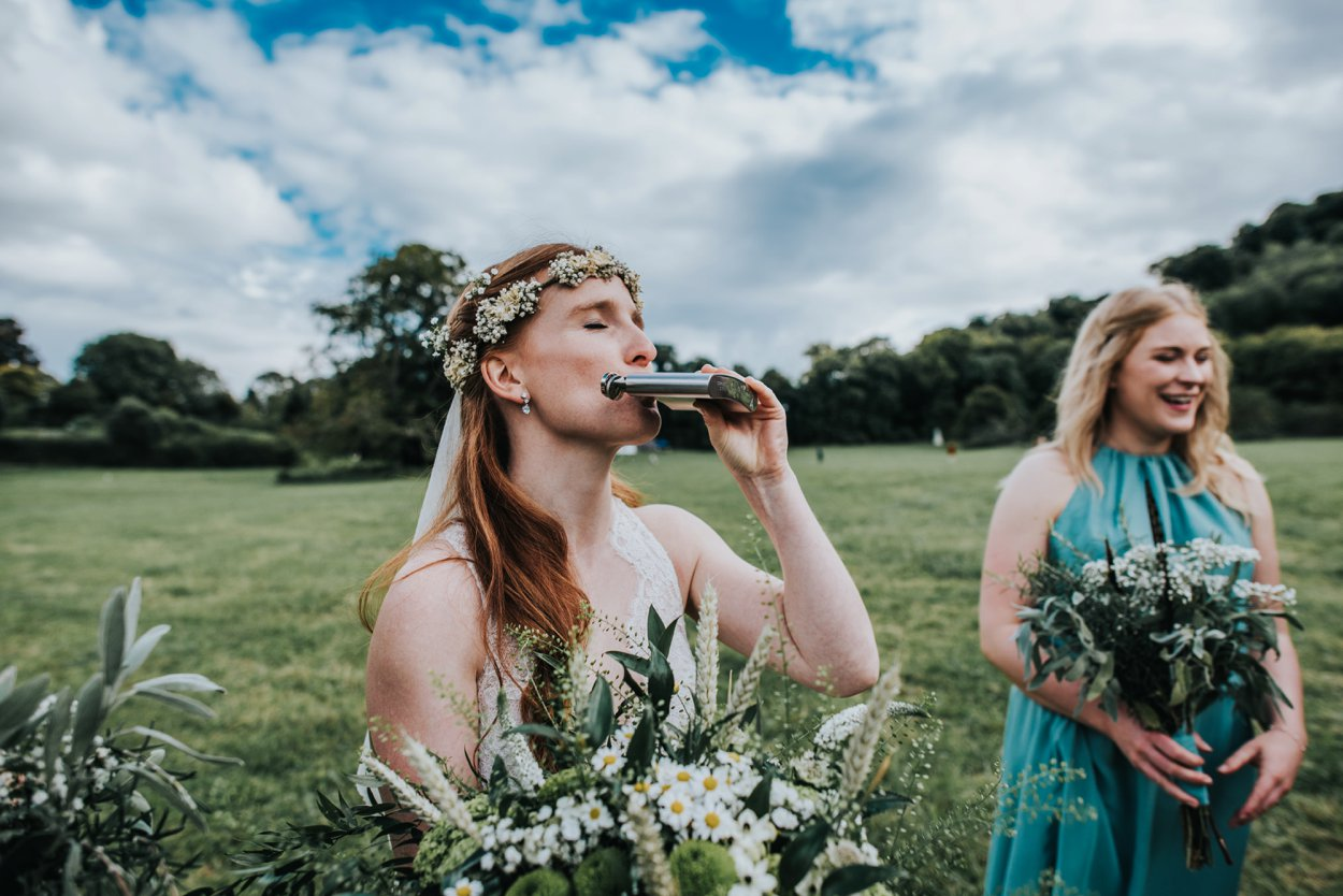 boho bride drinking from hip flask