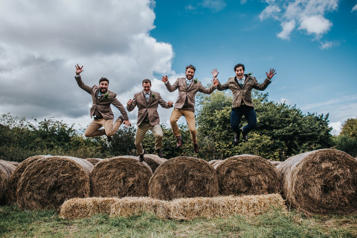 Groom in tweed suit jumping off hay bails with ushers