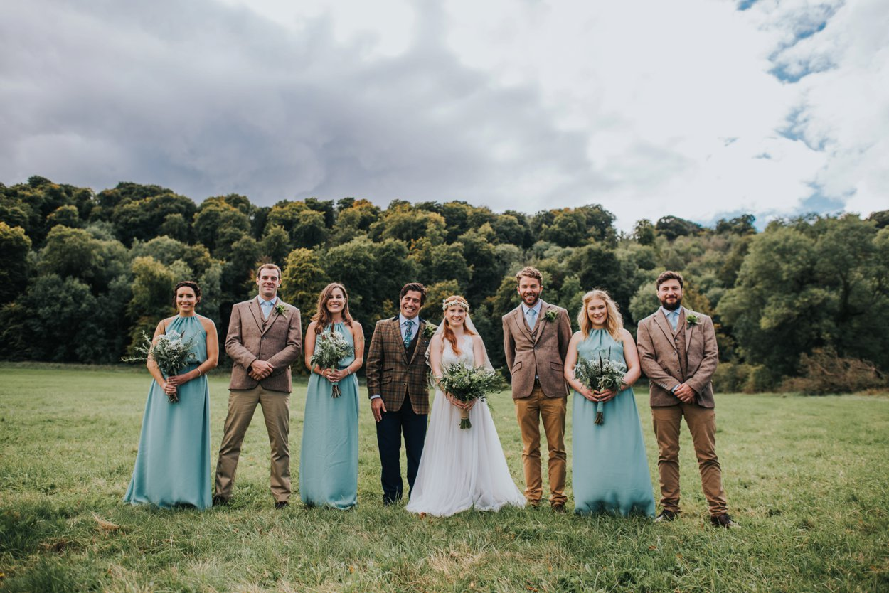 Boho bride and groom standing in field with friends
