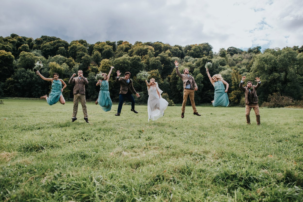 Boho bride and groom jumping in field, relaced wedding