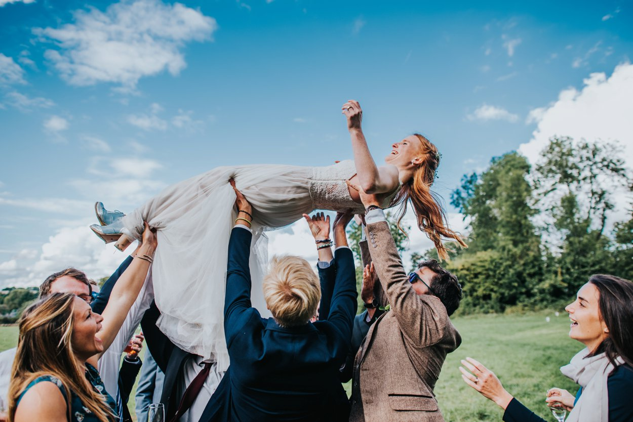 boho bride being lifted into the air by friends