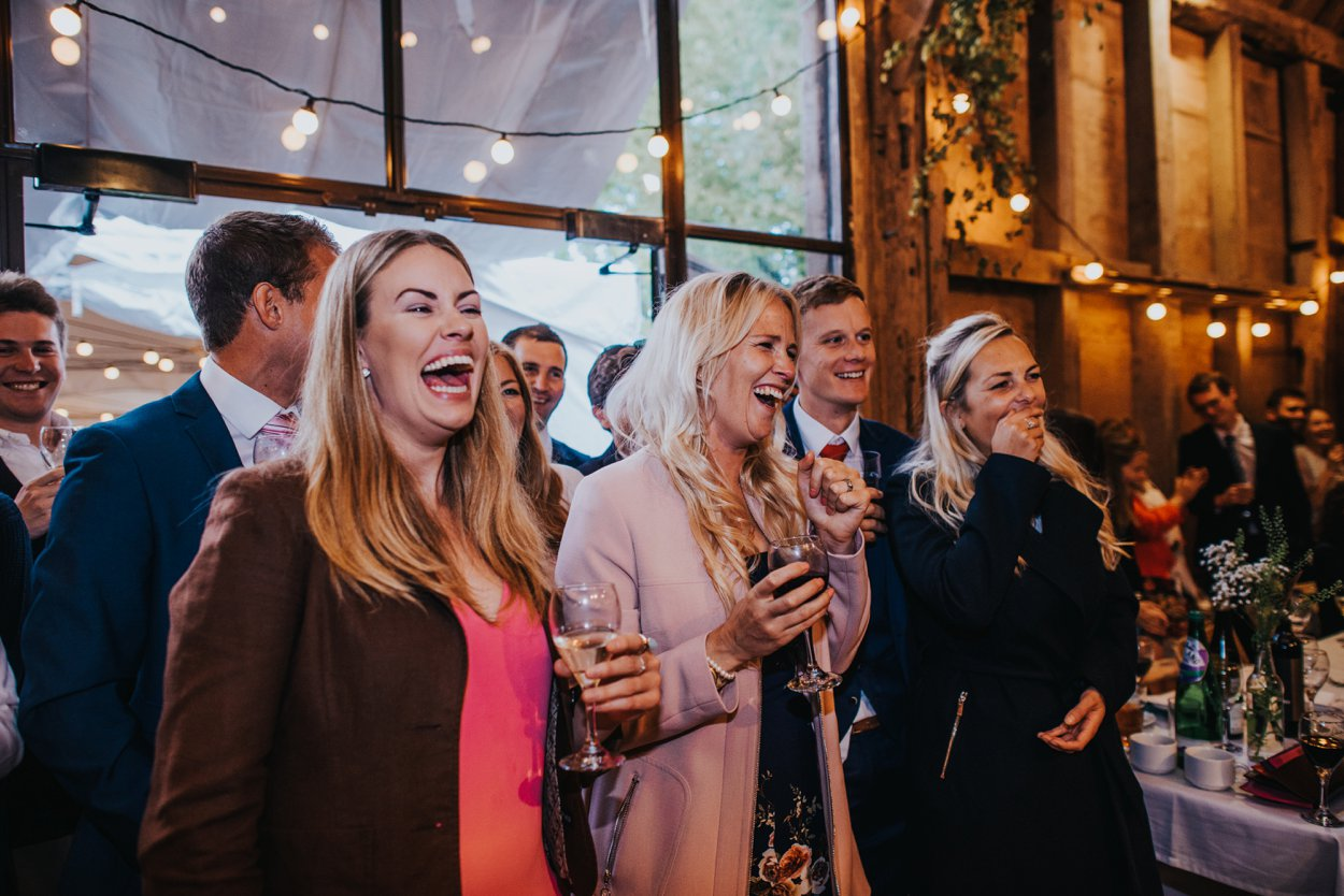 friends laughing at wedding speeches