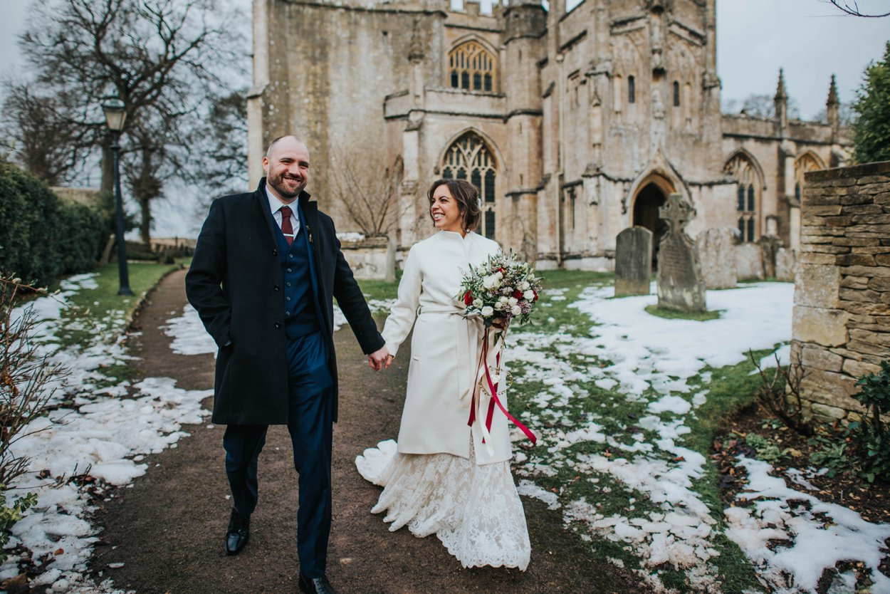 husband and wife leaving snowy church